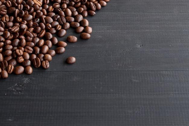 ソフトフォーカスとバックグラウンドで光の上の古い木の上のコーヒー豆 Premium写真