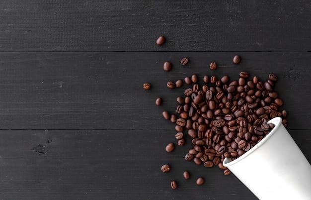 ホワイトペーパーカップと古い木製の背景のコーヒー豆。上面図 Premium写真