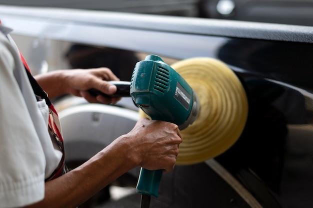 Крупным планом рука мужчина полирует черный автомобиль с полировщиком Premium Фотографии