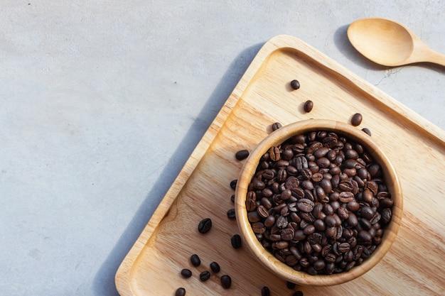 机の背景に木製のカップのコーヒー豆 Premium写真
