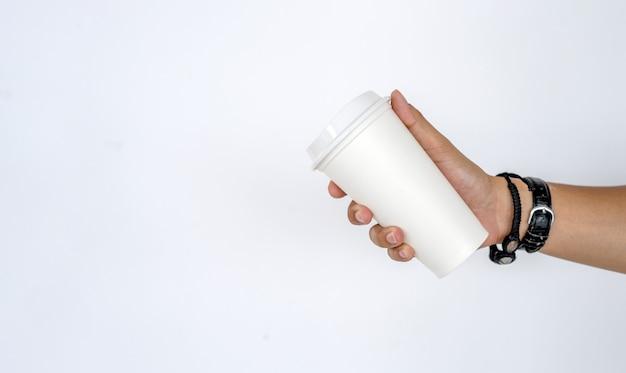 白い背景の上の熱いコーヒーカップを持っている男性の手のモックアップ Premium写真