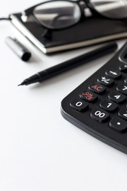 テキストのスペース、黒の本、眼鏡と白いテーブル上の電卓とオフィスの職場 Premium写真