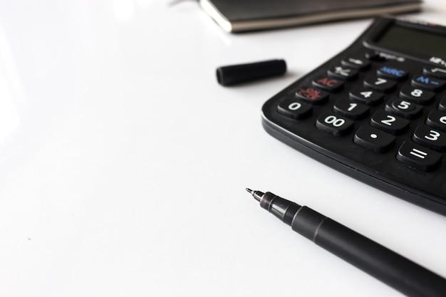 テキストスペース、黒の本と白いテーブル上の電卓とオフィスの職場 Premium写真
