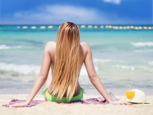 ビーチでビキニを着ている女性、サンデッキの座席。ビーチでリラックス Premium写真