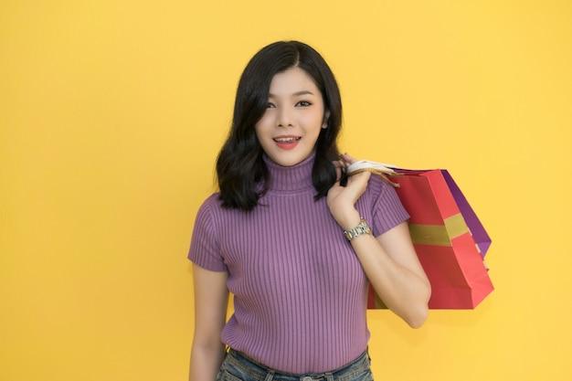 美しい女性は、クレジットカードを使用してショッピングモールで買い物をしています。 Premium写真
