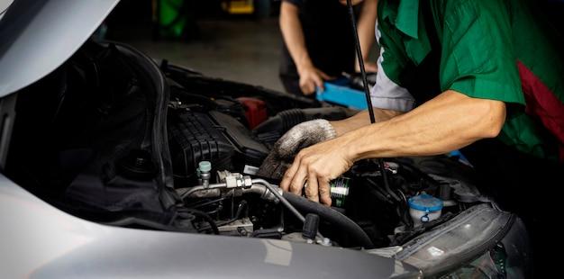 Автомеханик, меняющий масло, автомат. человек меняет моторное масло. замените моторное масло. замена автомобильного масла. проверьте автосервис. транспортно-ремонтный сервисный центр Premium Фотографии