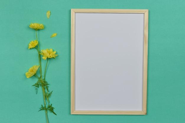 側に黄色の花と空の空白のフォトフレーム。 Premium写真