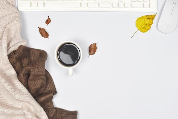 一杯のコーヒーとラップトップ、白の秋の紅葉のセーターコート。 Premium写真