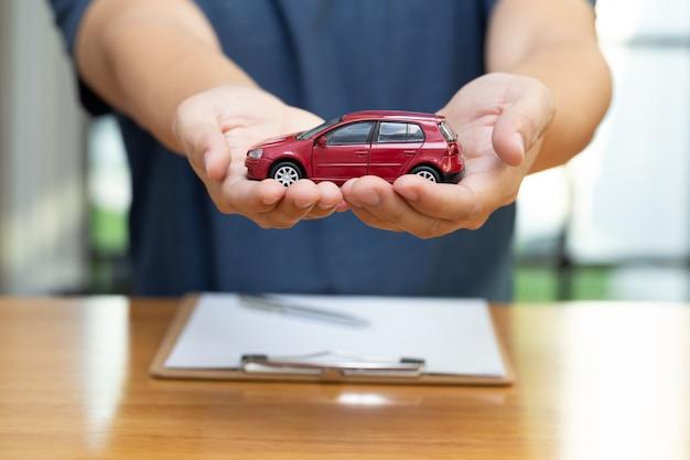 男性は、自動車および自動車保険、自動車コンセプトの保護との契約ポリシーを購入して署名することを選択しています Premium写真