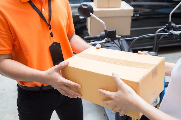 Женская рука принимает доставку коробок от доставщика, доставка товаров на мотоцикле, быстрый и бесплатный транспорт Premium Фотографии