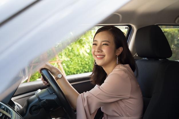 Азиатские женщины за рулем и счастливо улыбающиеся с радостным положительным выражением Premium Фотографии