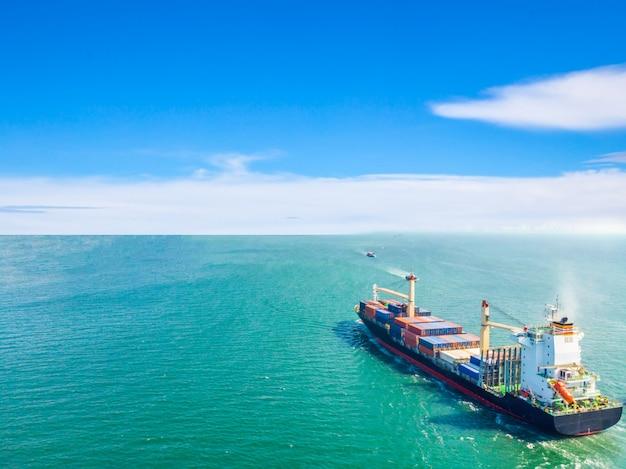 海の真ん中を航行する貨物船の空撮は、コンテナを港に輸送します。輸出入および海運業の物流および国際輸送の船による輸入 Premium写真
