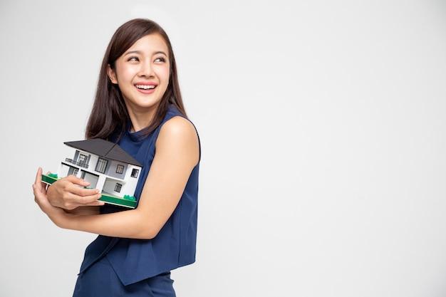 Молодая азиатская женщина усмехаясь и обнимая модель образца дома мечты Premium Фотографии
