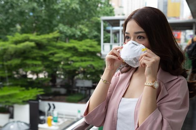 Азиатская бизнес-леди нося защитный лицевой щиток гермошлема на улице города с загрязнением воздуха. гигиеническая маска для лица для концепции экологической безопасности. Premium Фотографии
