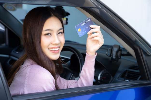 青い車の中に座って、クレジットカードを示す幸せな美しいアジアの女性は、オイルの支払い、タイヤの支払い、ガレージでのメンテナンス、ガソリンスタンドでの燃料補給車の支払い、自動車の融資 Premium写真