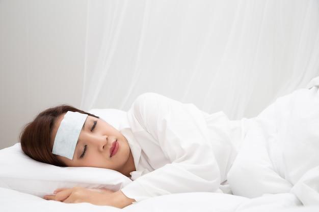 自宅の白いベッドで寝ている間に高熱を伴う若いアジアの女性、病気、発熱、咳、喉の痛みや感染症の細菌やウイルスによる病気など Premium写真
