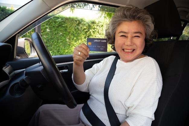 Счастливая старшая азиатская женщина сидя внутри автомобиля и показывая оплату кредитной карточки для масла, оплатить автошину, обслуживание на гараже, делает оплату заправляя автомобиль на бензоколонке, финансировании автомобиля Premium Фотографии