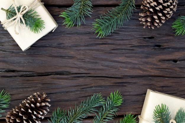 クリスマスと新年あけましておめでとうございます組成、ギフトボックス、松ぼっくり、木製のモミの枝の平面図とテキストのコピースペース Premium写真