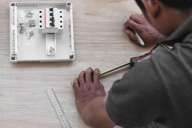 技術者が配電盤に回路ブレーカーを設計し設置する Premium写真