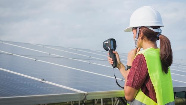 サーマルイメージャを使用して太陽電池パネルの温度熱をチェックする女性エンジニア Premium写真