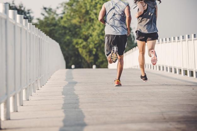 都市公園における道路を走っている若いカップルランナー Premium写真
