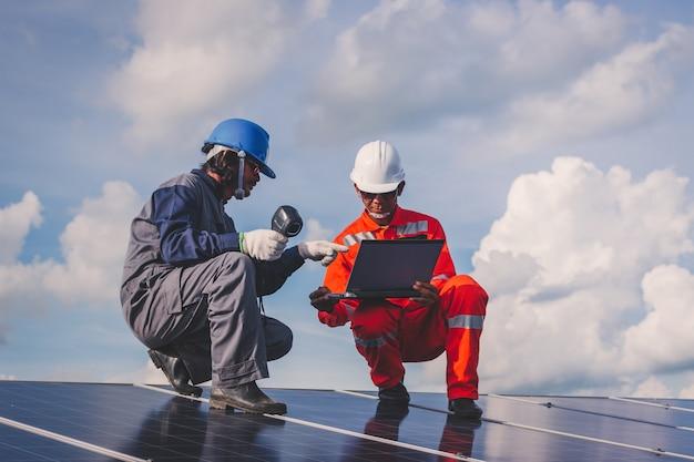太陽光発電所の運用とメンテナンス。太陽光発電所のチェックとメンテナンスに取り組んでいるエンジニアリングチーム、生活のためのグリーンエネルギーの革新への太陽光発電所 Premium写真