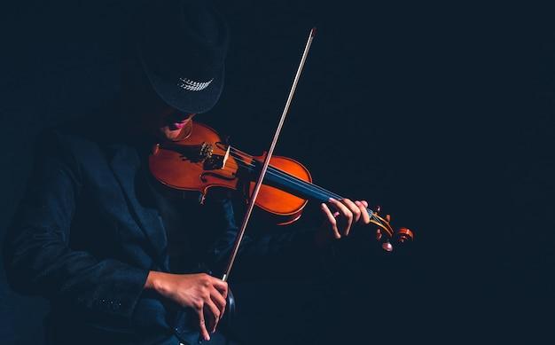 暗いスタジオのヴァイオリン・プレーヤー、ミュージカルコンセプト Premium写真