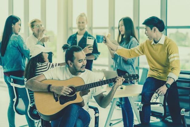 アジア人と多民族のビジネスの人々のグループの上にギターを演奏するアジア人労働者 Premium写真