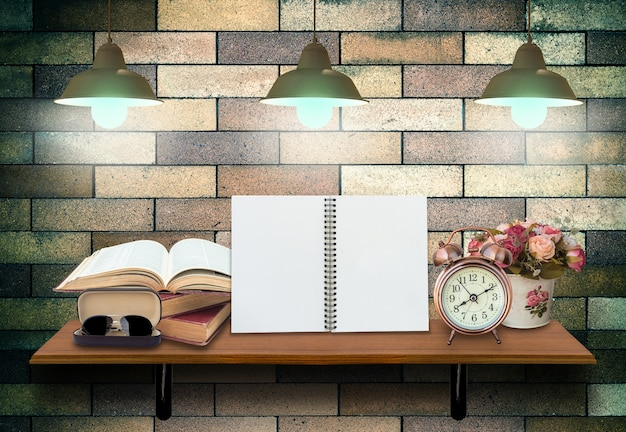 開いた本、目覚まし時計、眼鏡が付いた空のノートブックが付いているトップ木製棚 Premium写真