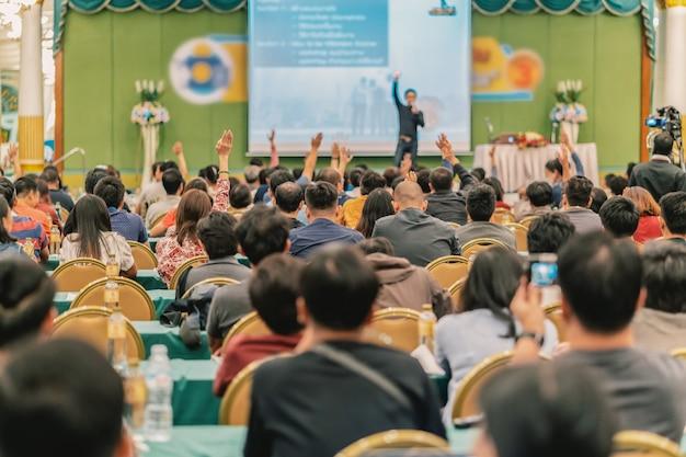 ステージ上のスピーカーからの質問に答えるための手を披露している視聴者のリアビュー Premium写真