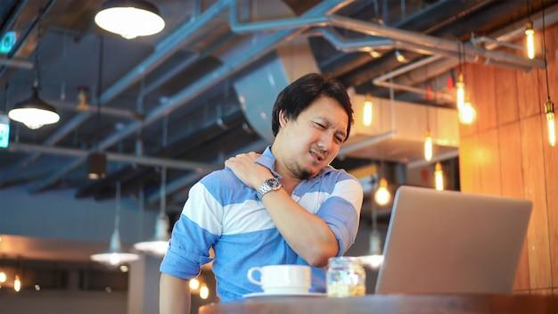 症状を持つカジュアルスーツで働くアジア人のビジネスマンは、頸痛、腰痛、頭痛 Premium写真