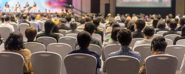 会議場のステージで聴衆を聴くスピーカーの背面図のバナーカバーページ Premium写真
