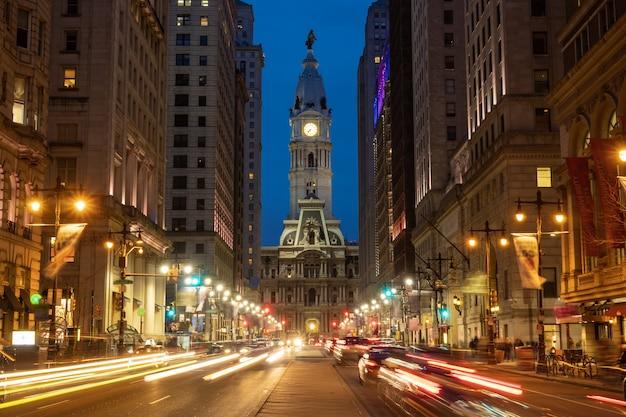 車の信号で夕暮れ時にフィラデルフィアの歴史的な歴史的な市庁舎の建物のシーン Premium写真