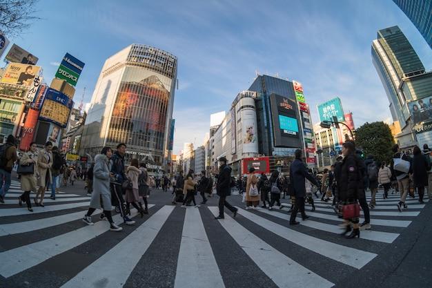 未定義の人々と車の群衆の魚眼レンズシーンは、歩行者専用交差点を歩いています。 Premium写真