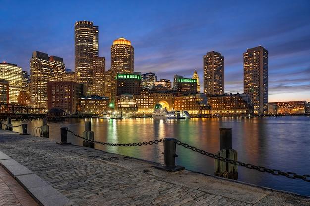 滑らかな水の川と幻想的な夕暮れ時にファン桟橋からボストンのスカイラインのシーン Premium写真