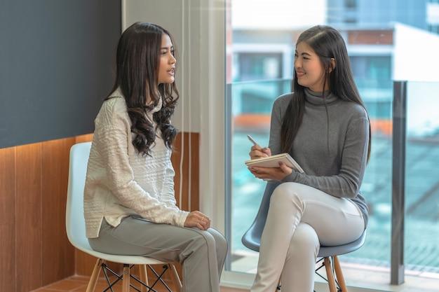アジアの女性プロの心理学者医師が居間で女性患者に相談 Premium写真