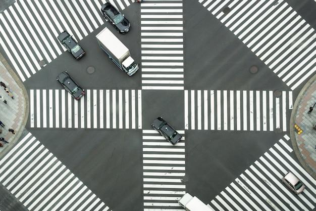 未定義の日本人の群衆の平面図は、建物の間の通りを横切るために歩いています Premium写真