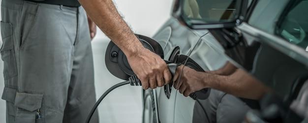 Перетяжка и обложка сцены. крупная рука техничной зарядки электромобиля в обслуживании. Premium Фотографии