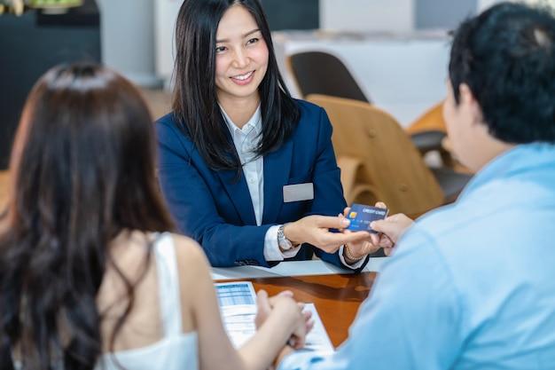 決定が新しい車を買うときにカップルの顧客からクレジットカードを受け取るアジアの店員 Premium写真