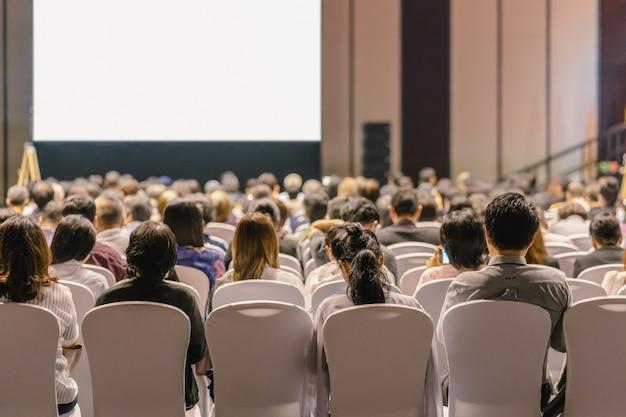 会議場やセミナーの会議でステージ上の聴衆の話を聞くスピーカーの背面図 Premium写真