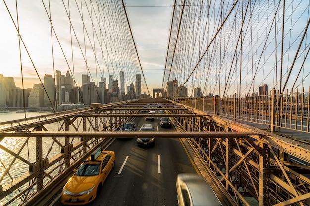 Движение в час пик после рабочего дня на бруклинском мосту через городской пейзаж нью-йорка Premium Фотографии