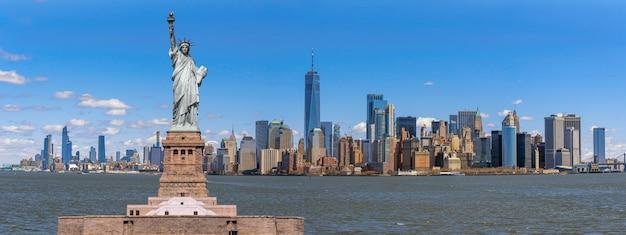 マンハッタン、アメリカ合衆国、アメリカ合衆国、建築、観光客と建物の場所であるニューヨーク市の景観川側のパノラマシーン上の自由の女神像 Premium写真