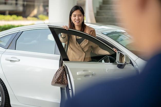 Портье приветствует азиатскую клиентку посетить центр технического обслуживания для проверки автомобиля в выставочном зале Premium Фотографии