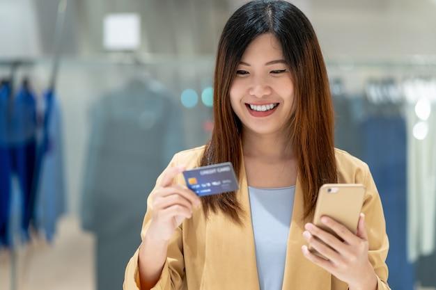デパートでのオンラインショッピングにスマートな携帯電話でクレジットカードを使用してアジアの女性 Premium写真