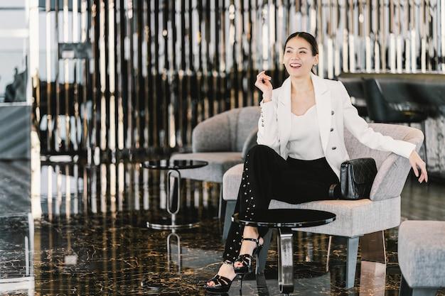 モダンなロビー、オフィスやコワーキングスペース、コーヒーブレークレジャー、ファッション、勤務時間、ビジネス人々の概念の後のライフスタイルのソファーに座っているフォーマルなスーツを着て肖像アジア女性実業家 Premium写真
