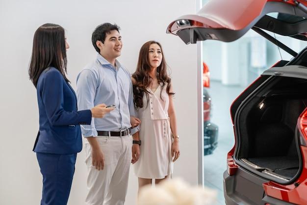 Азиатская продавщица демонстрирует особенности автомобиля в багажнике, чтобы объединить клиентов в концепции автосалона, службы поддержки и торгового представителя. Premium Фотографии