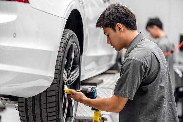 アジアのメカニックは、メンテナンスサービスセンターで車のホイールをチェックします Premium写真