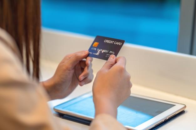 Женщина крупного плана азиатская используя кредитную карточку с таблеткой для онлайн покупок в универмаге над стеной магазина одежды, бумажником денег технологии и концепцией онлайн оплаты, модель-макетом кредитной карточки Premium Фотографии