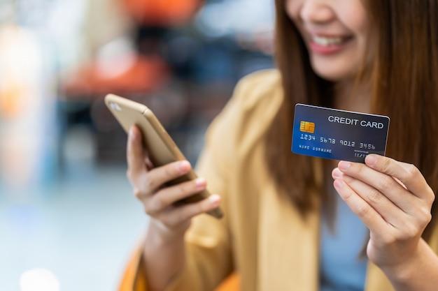 クローズアップアジアの女性の手はクレジットカードを保持し、洋服店の壁、技術お金財布、オンライン支払いの概念上のオンラインショッピングのための携帯電話を提示 Premium写真