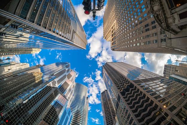 空、イリノイ州、アメリカ合衆国、ビジネスと視点の上を飛んでいる飛行機がある高層ビルの間で雲の反射とダウンタウンシカゴの高層ビルの魚眼シーンと蜂起角度 Premium写真